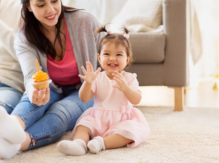 baby girl with mother at home birthday party Stock Photo
