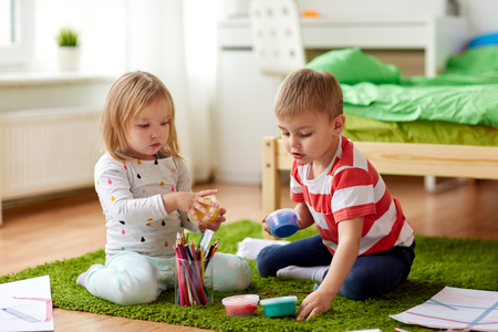 kids with modelling clay and crayons at home 스톡 콘텐츠