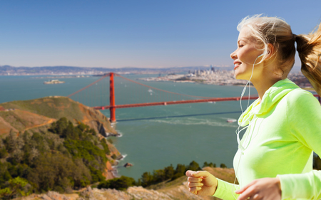 fitness, sport and technology concept - happy woman running and listening to music in earphones over golden gate bridge in san francisco bay background
