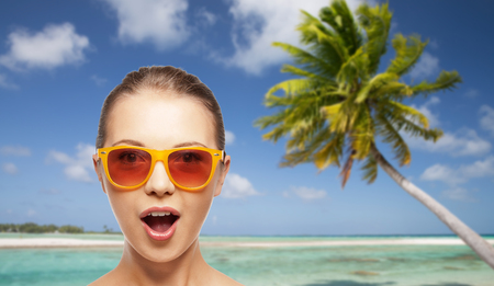 travel, tourism, summer holidays, vacation and people concept - amazed young woman or teenage girl in sunglasses over exotic tropical beach background