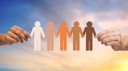 population, race and ethnicity concept - multiracial couple hands holding chain of people pictogram over evening sky background Stock Photo