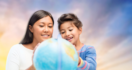 family, education, travel and people concept - mother and daughter with globe over evening sky background