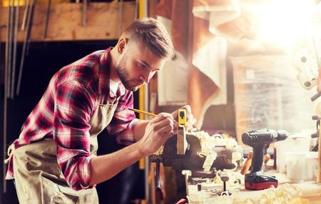 Profesión, carpintería, carpintería y concepto de personas - carpintero con regla midiendo tablón de madera en el taller