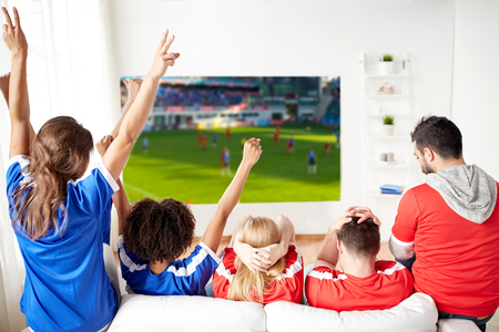 sport, leisure and entertainment concept - happy friends or football fans watching soccer on projector screen at home and celebrating victory 스톡 콘텐츠