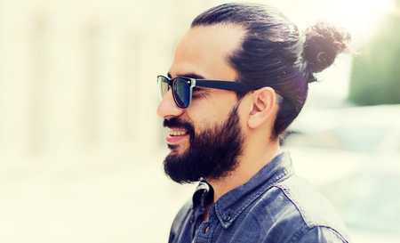 lifestyle, emotion, expression and people concept - happy smiling man with beard and sunglasses on city street Stock Photo