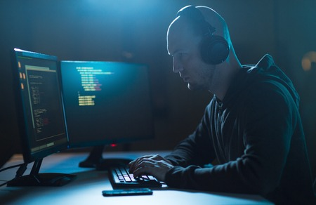 cybercrime, hacking and technology concept - male hacker with headphones and coding on laptop computer screen wiretapping or using computer virus program for cyber attack in dark room Stock Photo