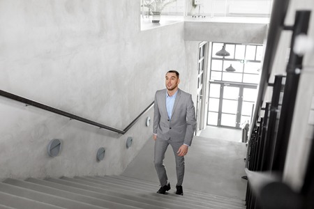 business, success and career lift concept - businessman walking upstairs Фото со стока