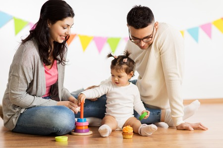 baby girl with parents playing with pyramid toy