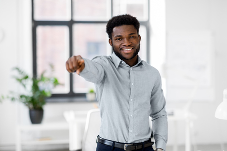 african businessman at office pointing at you