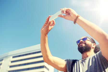 man taking video or selfie by smartphone in city