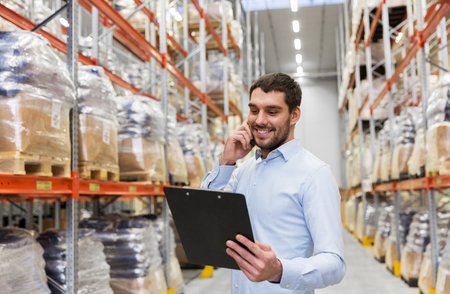 businessman calling on smartphone at warehouse Stock Photo