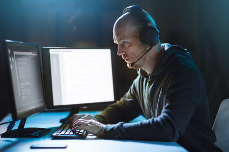 hacker with computer and headset in dark room