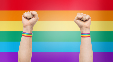 hands with gay pride rainbow wristbands shows fist Stock Photo