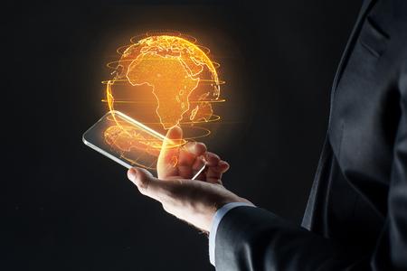 main avec smartphone et hologramme de la terre Banque d'images