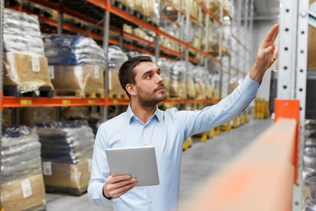 businessman with tablet pc at warehouse Banco de Imagens