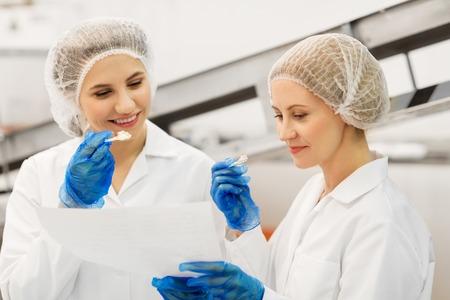 vrouwelijke technologen die ijs proeven in de fabriek