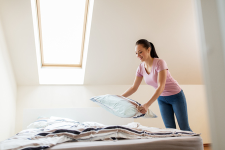 happy woman or housewife making bed at home Stock Photo