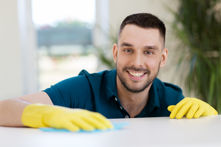 smiling man cleaning table with cloth at home