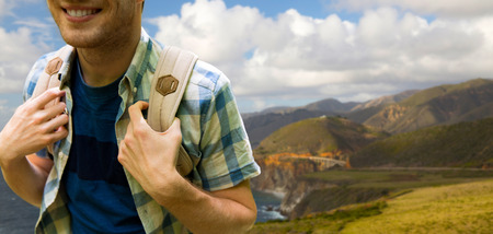 close up of man with backpack over big sur coast