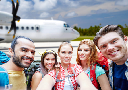 friends with backpack taking selfie over plane