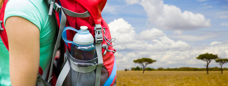 close up of woman with water bottle in backpack