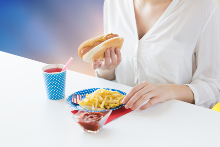 close up of woman eating hotdog and french fries Stock Photo