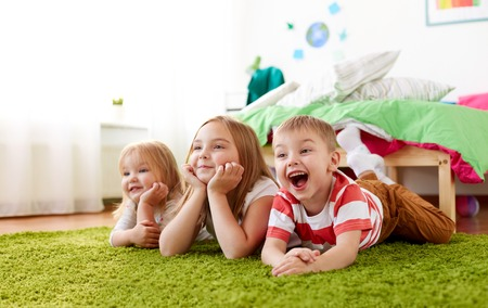 happy little kids lying on floor or carpet