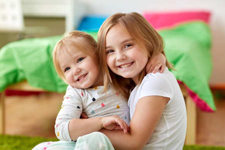happy little girls or sisters hugging at home