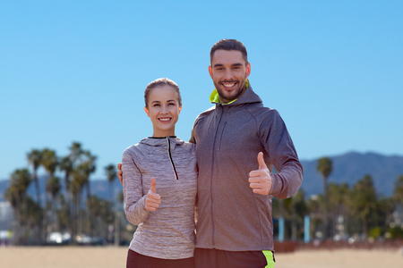 smiling couple in sport clothes showing thumbs up Stock Photo