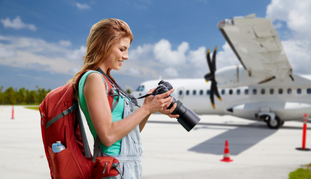 woman with camera and backpack traveling by plane