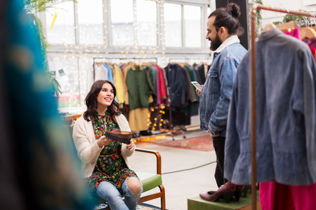 couple choosing footwear at vintage clothing store Stock Photo