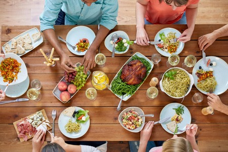 group of people eating at table with food Banco de Imagens - 101764149