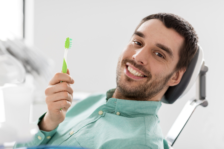 smiling man with toothbrush at dental clinic Stock Photo