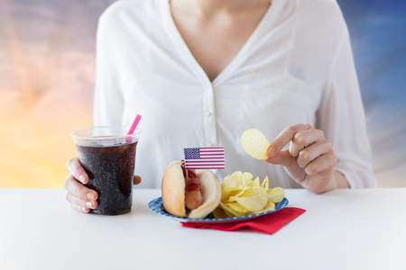 close up of woman eating hot dog with cola