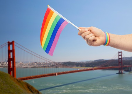 hand with gay pride rainbow flag and wristband