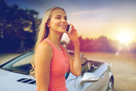 woman calling on smartphone at convertible car