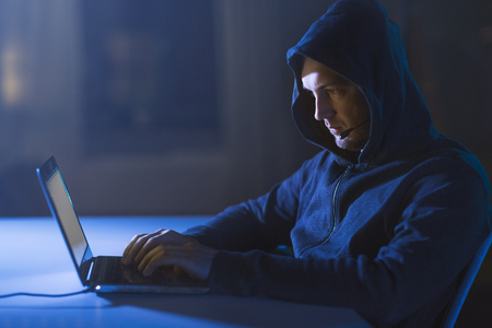 hacker with microphone and laptop in dark room
