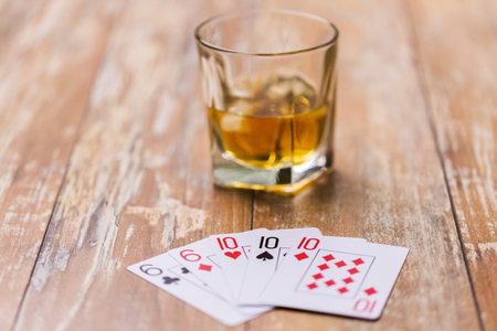 glass of whisky and playing cards on table Stock Photo