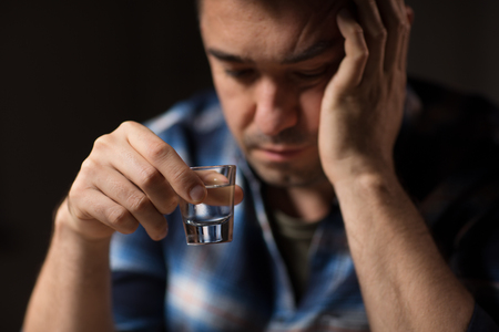 close up of man drinking alcohol or vodka at night