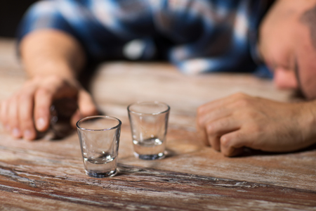 drunk man with empty glasses on table at night Stock Photo - 101798014