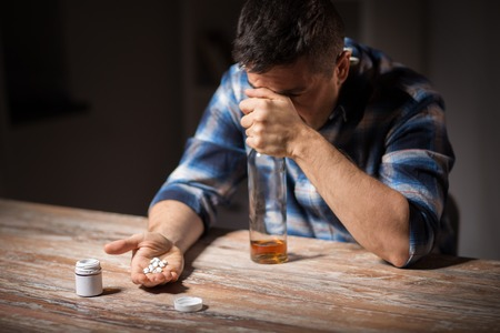 unhappy drunk man with bottle of alcohol and pills