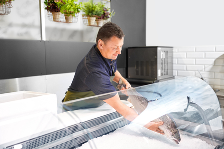 male seller putting trout to fridge at fish shop Stockfoto