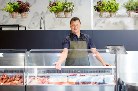 male seller showing seafood at fish shop fridge Stock Photo