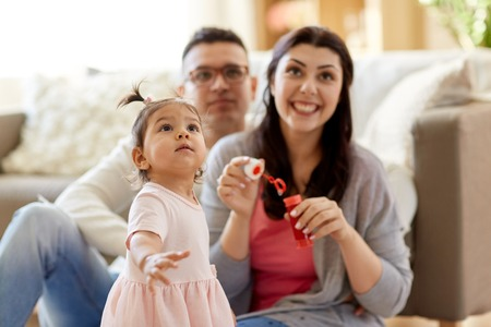 family with soap bubbles playing at home Stock Photo