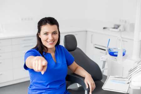 female dentist or nurse at dental clinic office Stock Photo