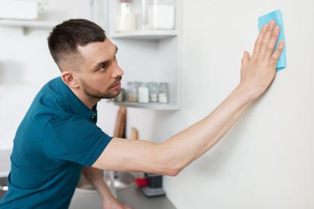Hombre con trapo de limpieza de pared en la cocina de casa Foto de archivo