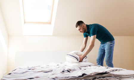 happy man making bed at home Stock Photo