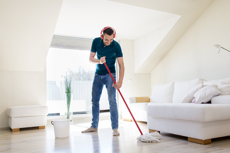 man in headphones cleaning floor by mop at home