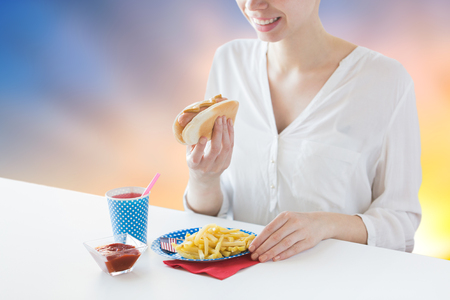 fast food and people concept - close up of happy woman eating hot dog and french fries with lemonade in paper cup over evening sky background Stock Photo