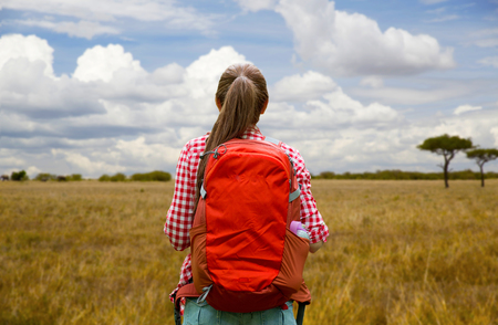 adventure, travel, tourism, hike and people concept - young woman with backpack over african savannah background